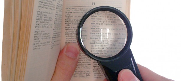 Hands holding a magnifying glass over a page of a dictionary