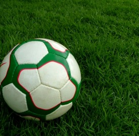 a football on a green football soccer pitch