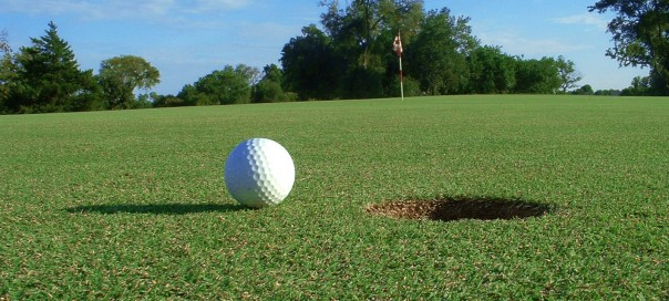 A golf ball teeters near the hole as apparently humankind does with the end of the world supposedly approaching