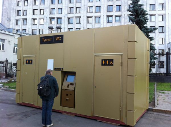 A potential customer studies new pay toilets, with Ministry of Defence in the background. VOA Photo: James Brooke