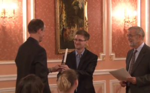 At a Moscow dinner Oct. 9, Robert Drake (ex-NSA) hands to Edward Snowden (ex-NSA) a candlestick, symbolic of the Sam Adams award, which seeks to illuminate dark corners. Still from WikiLeaks video.