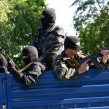 Armed pro-Russian rebel squat in the bed of a truck outside a military academy which houses weapons in Donetsk on May 6.