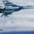 A Russian SU-27 Flanker aircraft banks away with a RAF Typhoon in the background. RAF Typhoons were scrambled on June 17 to intercept multiple Russian aircraft in international airspace