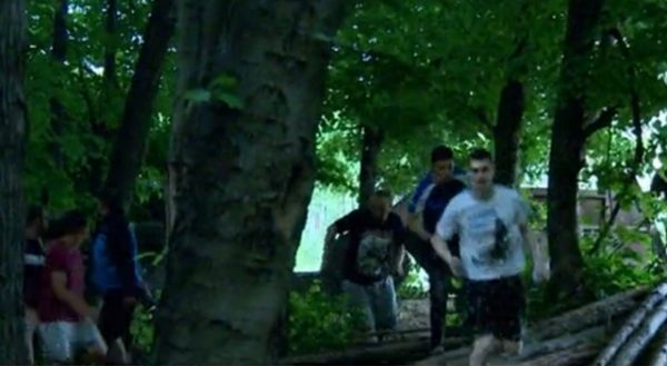 Youths disperse through the trees as police intervene in Orlandovtsi, June 14.