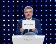 IOC president Thomas Bach shows the results of the election of the Host City of the 2022 Olympic Winter Games. Photo: IOC/Ubald Rutar