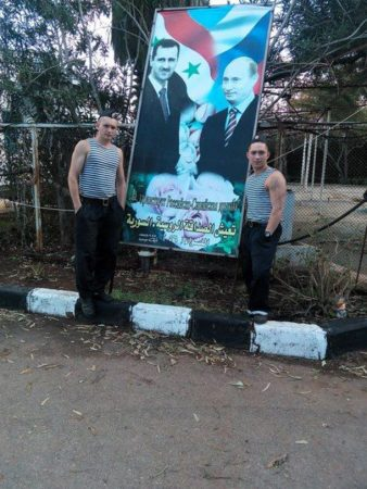 Russian soldiers posing in Syria next to the banner showing Russian President Vladimir Putin and his Syrian counterpart Bashar al-Assad.