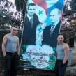 Russian soldiers posing in Syria next to the banner showing Russian President Vladimir Putin and his Syrian counterpart Bashar al-Assad.-crop