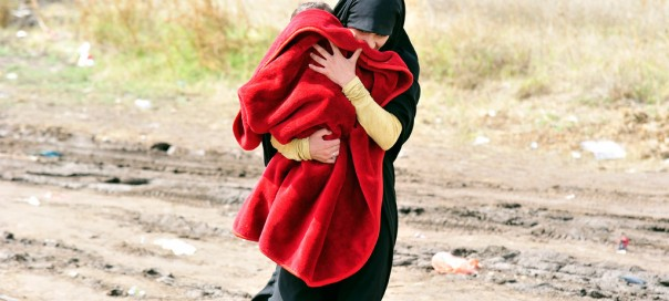 A woman carrying a child under a blanket walks on a muddy path in the southern Serbian town of Preševo, on the border with the former Yugoslav Republic of Macedonia. Photo: UNICEF/Tomislav Georgiev