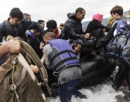 A group of refugees disembark an inflatable boat after reaching the Greek island of Lesvos photo UNHCR Achilleas Zavallis