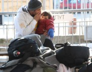 A man and child try to keep warm as they wait at the migrant and refugee registration center in Presevo Serbia Photo P Walter Wellman VOA