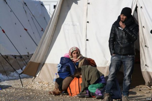 A refugee family waits to leave Presevo, Serbia, for Western Europe. Photo: P Walter Wellman/VOA