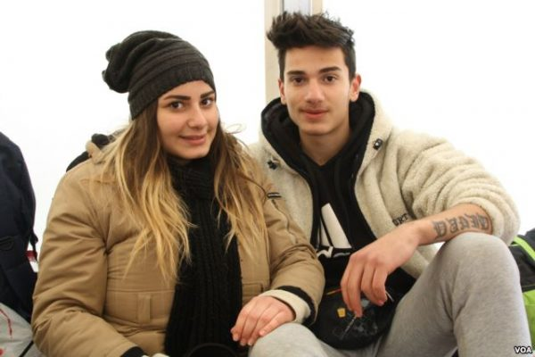 Christina and David Bshara wait in Presevo, Serbia, while traveling to Germany to reunite with their mother. Photo: P Walter Wellman/VOA