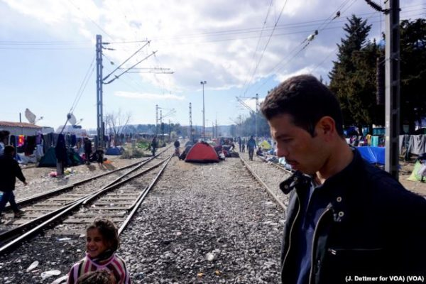 A man walks amid a makeshift encampment with tents set up between train tracks in the northern Greek border town of Idomeni photo Jamie Dettmer VOA
