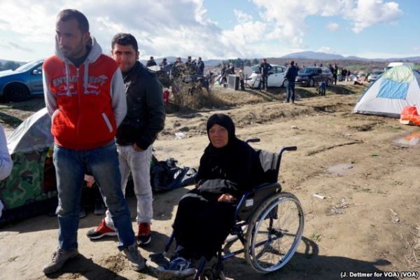 A wheelchair-bound migrant woman waits in the makeshift refugee camp in the Idomeni, Greece, near its border with Macedonia photo Jamie Dettmer VOA