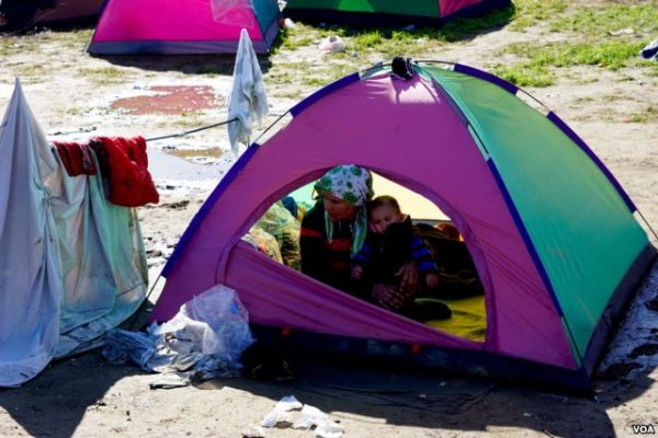 A woman and child huddle in a tent in a makeshift encampment in Idomeni, Greece, waiting for permission to move onto other points in Europe photo Jamie Dettmer VOA