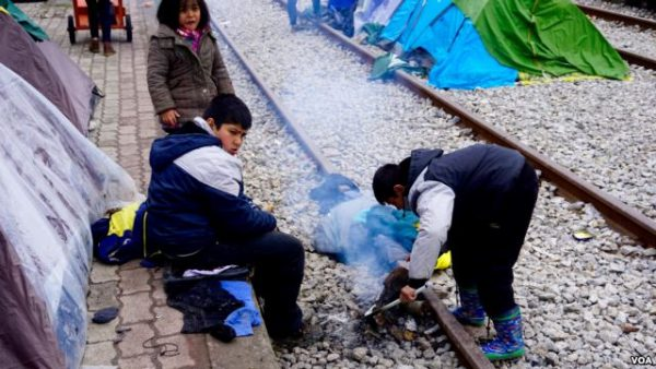 Children along tracks that lead to the Macedonian border attempt to light fire to stay warm, in Idomeni, Greece, March 16 2016. Photo: Jamie Dettmer/VOA