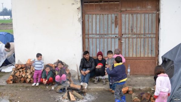 A Refugee family attempts to stay warm not far from Macedonian border, in Idomeni, Greece. Photo: Jamie Dettmer/VOA