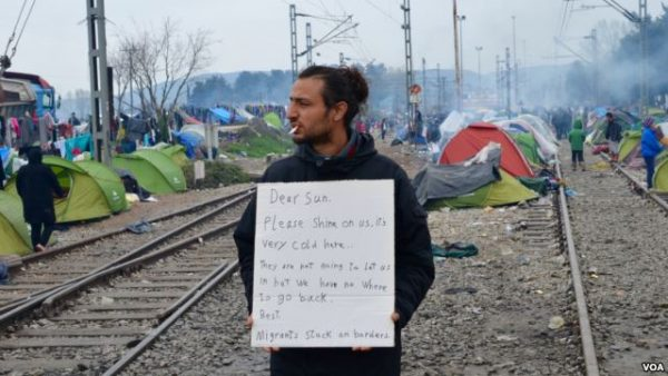 A man shares message of collective despair taking hold at makeshift refugee camp along Greek-Macedonian border, in Idomeni. Photo: Jamie Dettmer/VOA