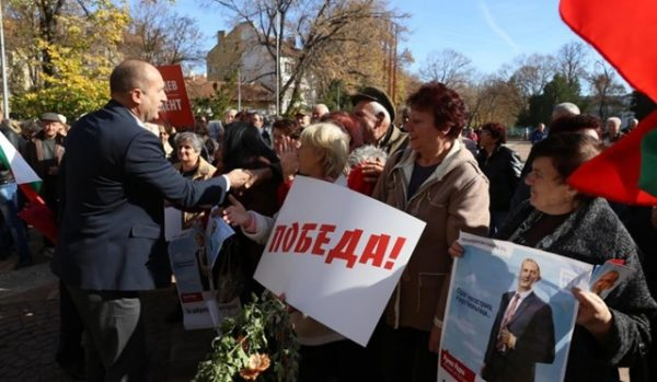 Bulgarian Socialist Party candidate Roumen Radev greets supporters, one holding a poster reading 'Victory!'